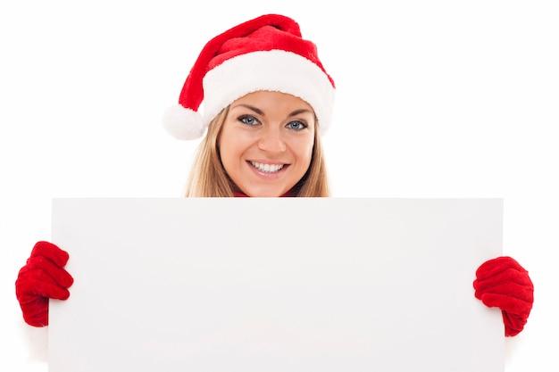 Mujer de navidad con tablero en blanco