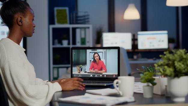 Mujer de negocios africana discutiendo con su socio de forma remota en línea sentado frente a la computadora portátil que trabaja en la oficina de puesta en marcha hablando por videollamada durante la reunión virtual a la medianoche, usando auriculares