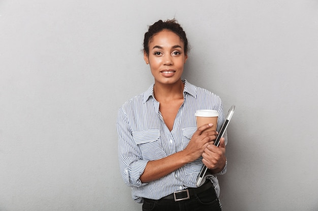Mujer de negocios africana joven atractiva con camisa que se encuentran aisladas, sosteniendo la tableta, bebiendo café para llevar