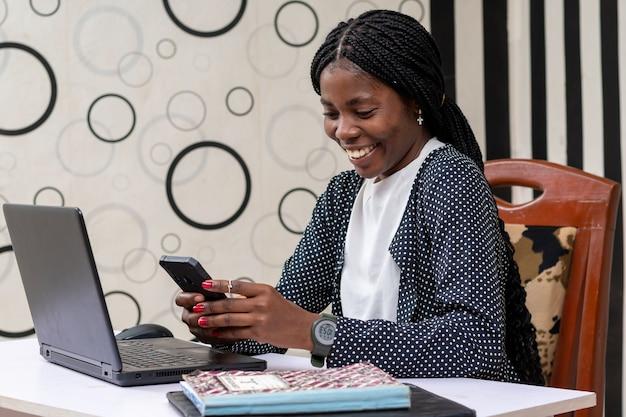 Mujer de negocios africana joven que se siente muy feliz por las noticias que vio en su teléfono celular
