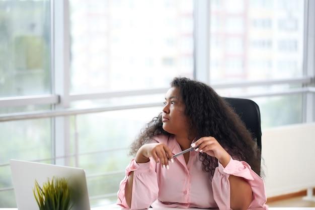 Mujer de negocios afro en camisa sentado en la mesa junto a la ventana y usando la computadora portátil en la oficina.