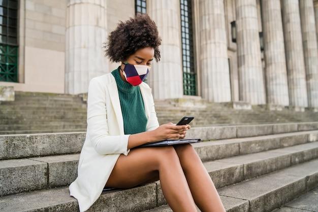 Mujer de negocios afro con máscara protectora y usando su teléfono móvil mientras está sentada en las escaleras al aire libre en la calle. concepto urbano y empresarial.