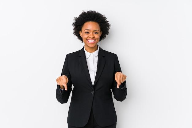 La mujer de negocios afroamericana envejecida media contra una pared blanca aisló puntos abajo con los dedos, sensación positiva.