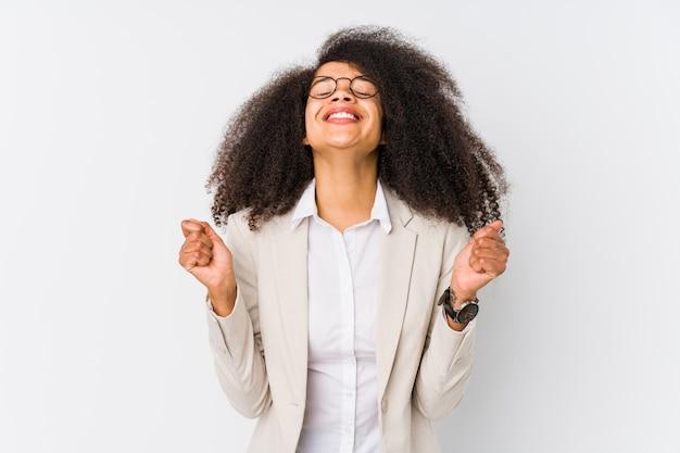 Mujer de negocios afroamericana joven levantando el puño, sentirse feliz y exitoso. concepto de victoria