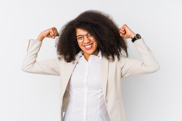 Mujer de negocios afroamericana joven que muestra gesto de fuerza con los brazos, símbolo del poder femenino