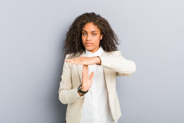 Mujer de negocios afroamericana joven que muestra un gesto de tiempo de espera.