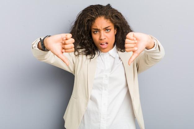Mujer de negocios afroamericana joven que muestra el pulgar hacia abajo y que expresa aversión.
