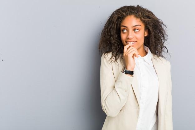 La mujer de negocios afroamericana joven se relajó pensando en algo que miraba un espacio de la copia.