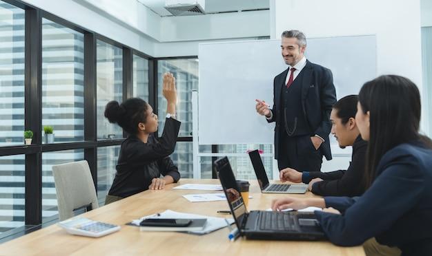 Mujer de negocios afroamericana levantando la mano pidiéndole a su jefe mientras se reúne con colegas en la oficina