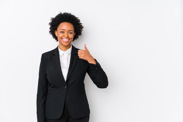 Mujer de negocios afroamericana de mediana edad contra un blanco aislado sonriendo y levantando el pulgar hacia arriba