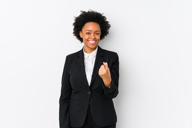 Mujer de negocios afroamericana de mediana edad contra una pared blanca aislada apuntando con el dedo a usted como si invitara a acercarse.
