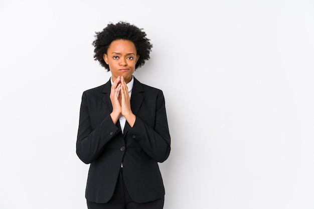 Mujer de negocios afroamericana de mediana edad contra una pared blanca aislada haciendo plan en mente, creando una idea.