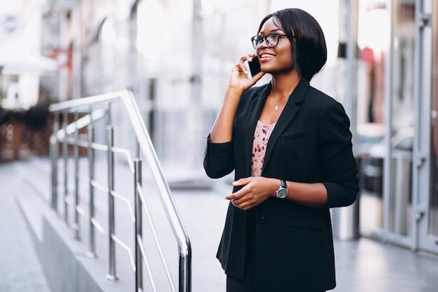 Mujer de negocios afroamericana con teléfono