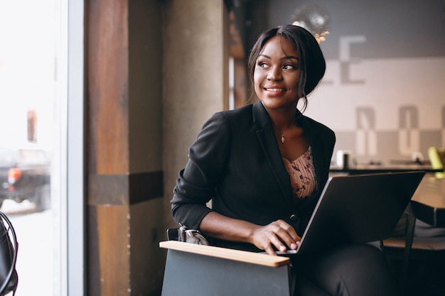 Mujer de negocios afroamericana trabajando en una computadora en un bar