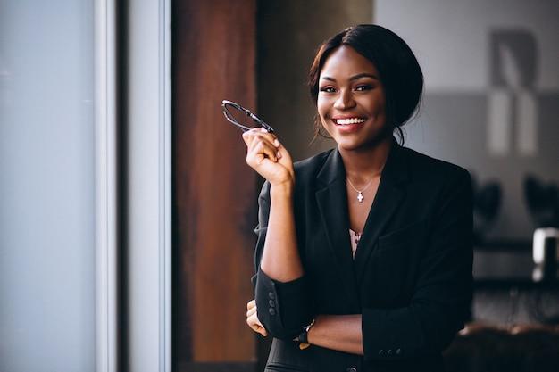 Mujer de negocios afroamericana por la ventana