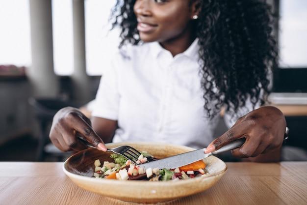 Mujer de negocios afroamericano comiendo ensalada en un café cerca