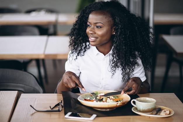 Mujer de negocios afroamericano comiendo ensalada en un café