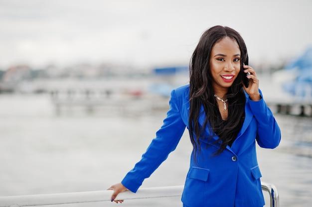Mujer de negocios afroamericano de éxito en traje azul con teléfono móvil.