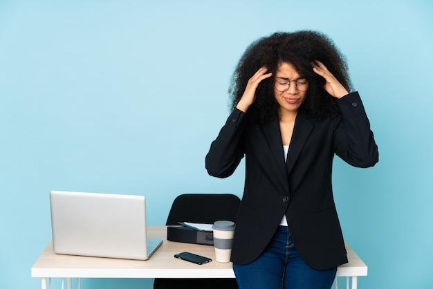 Mujer de negocios afroamericano que trabaja en su lugar de trabajo con dolor de cabeza