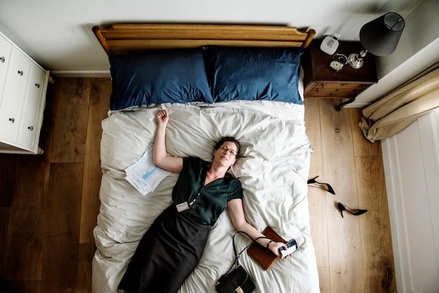 Mujer de negocios agotada que se duerme tan pronto como regresó a casa
