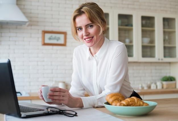 Mujer de negocios alegre con café usando la computadora portátil
