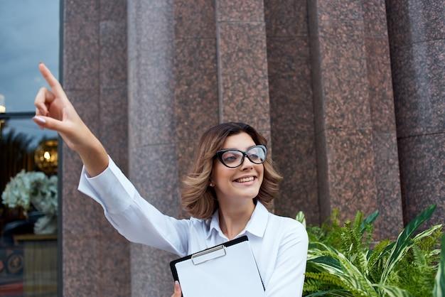 Mujer de negocios alegre en la calle con trabajo de documentos