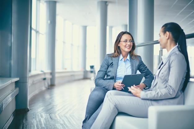Mujer de negocios alegre hablando con su compañera