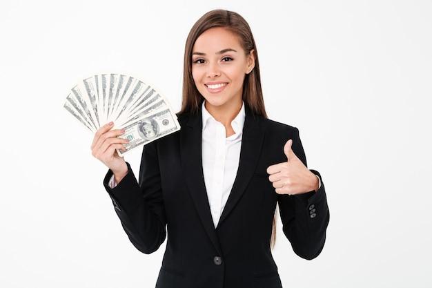 Mujer de negocios alegre mostrando pulgares arriba sosteniendo dinero