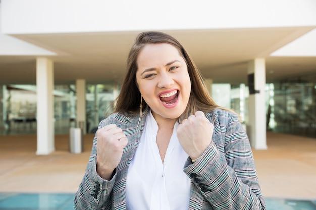 Mujer de negocios alegre que bombea los puños al aire libre
