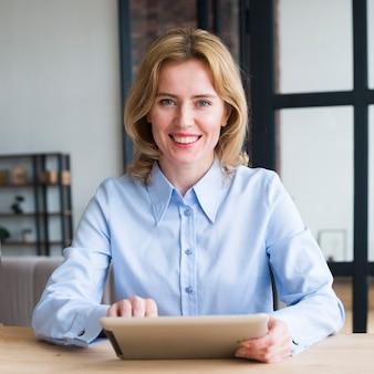 Mujer de negocios alegre que usa la tableta en la tabla