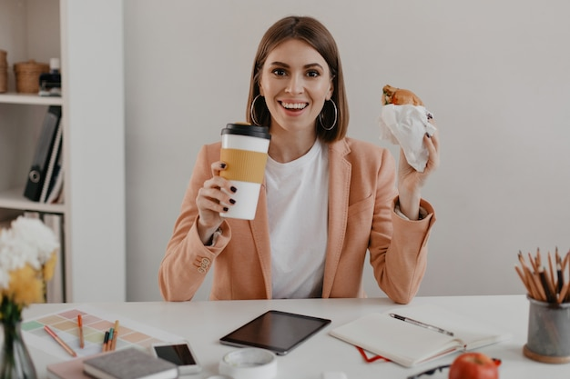 Mujer de negocios alegre con una sonrisa mientras almuerza en la oficina brillante.