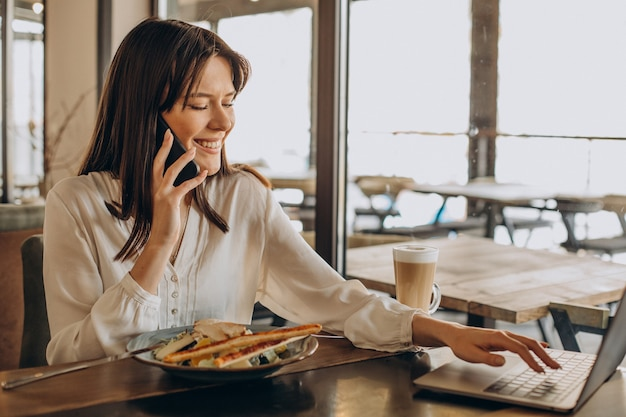 Mujer de negocios almorzando en un café y trabajando en equipo