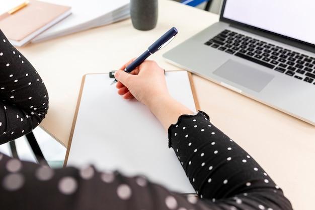 Mujer de negocios de alto ángulo tomando notas en el portapapeles