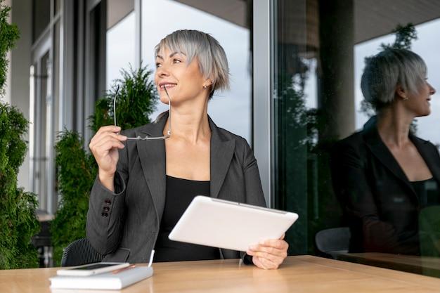 Mujer de negocios de ángulo bajo mirando a otro lado