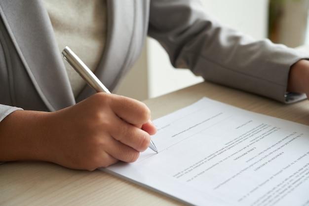 Mujer de negocios anónima recortada que comprueba el acuerdo antes de firmar