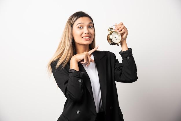 Mujer de negocios apuntando a un reloj de alarma en la pared blanca.