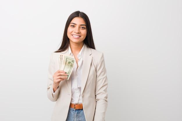 Mujer de negocios árabe joven que lleva a cabo dólares felices, sonrientes y alegres.