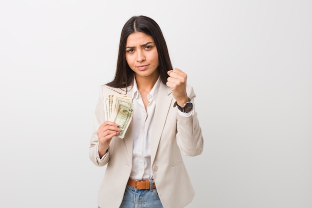 Mujer de negocios árabe joven que lleva a cabo dólares que muestran el puño con la expresión facial agresiva.