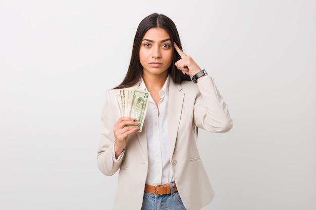 Mujer de negocios árabe joven que lleva a cabo dólares que señalan su templo con el dedo, pensando, centrado en una tarea.
