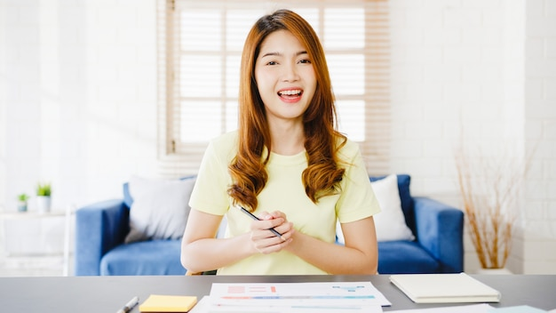 Mujer de negocios de asia con computadora portátil hablar con colegas sobre el plan en la reunión de videollamada mientras trabaja desde casa en la sala de estar autoaislamiento, distanciamiento social, cuarentena por coronavirus.