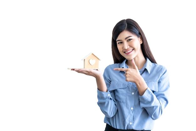 Mujer de negocios asiática atractiva mostrar y sosteniendo el modelo de casa sobre fondo blanco aislado
