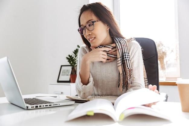 Mujer de negocios asiática complacida en anteojos usando una computadora portátil mientras está sentado junto a la mesa en la oficina
