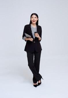 Mujer de negocios asiática confiada sonriente que sostiene el café y la tableta sobre fondo gris.