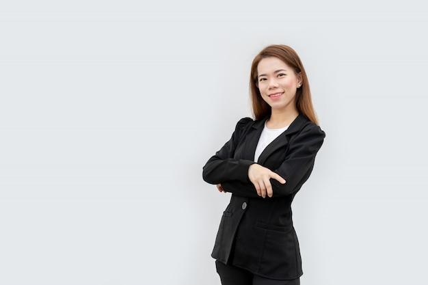Mujer de negocios asiática cruzó los brazos con el pelo largo en traje negro aislado en color blanco