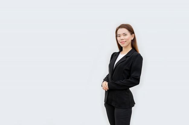 Mujer de negocios asiática cruzó las manos de pie con el pelo largo en traje negro aislado en color blanco