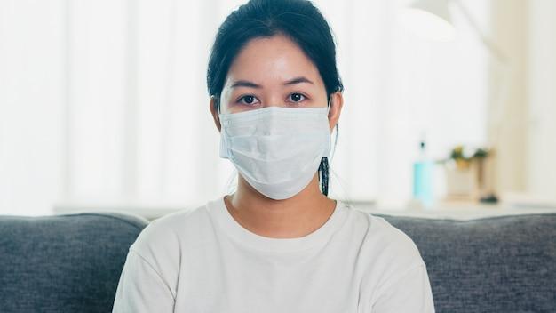 Mujer de negocios asiática deprimida con máscara protectora sentado en el sofá en la sala de estar en casa cuando el distanciamiento social se queda en casa y el tiempo de cuarentena, pandemia en china, concepto de coronavirus.