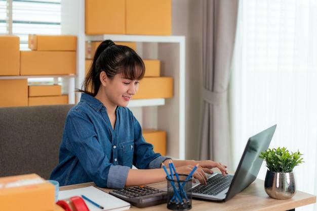 La mujer de negocios asiática del dueño del adolescente trabaja en casa para las compras en línea