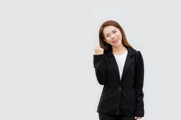 La mujer de negocios asiática feliz arma para arriba en el traje negro aislado en el color blanco