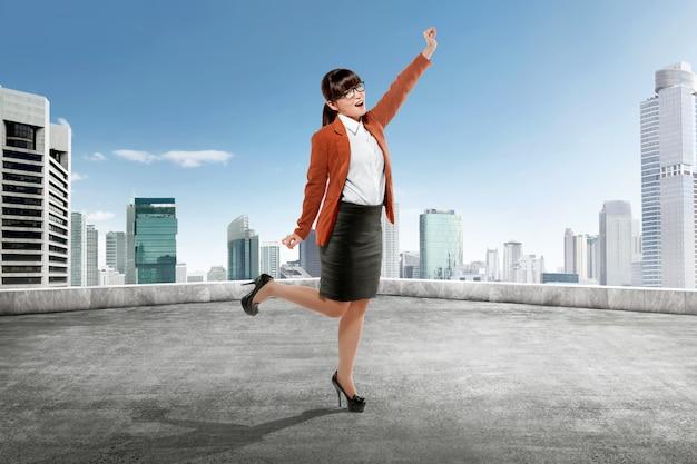 Mujer de negocios asiática feliz que se coloca en el tejado