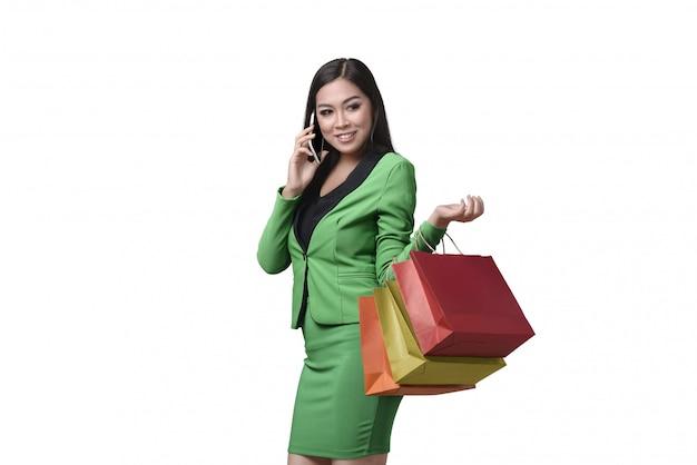Mujer de negocios asiática hermosa que sostiene el panier mientras que habla en su teléfono móvil